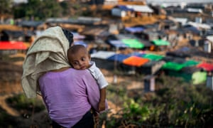 A Rohingya woman holds a baby in her arms at Kutupalong Rohingya refugee camp in Coxs Bazar.