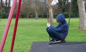 Boy sitting on a swing in a playground