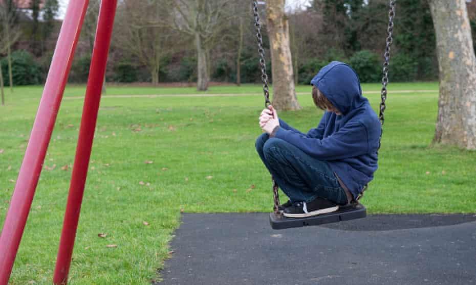 Boy sitting on swing in playground