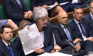Theresa May holding an advert placed by Labour peers attacking Jeremy Corbyn's record on antisemitism at PMQs.