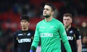Swansea City players including goalkeeper Lukasz Fabianski look dejected after defeat to Stoke City.