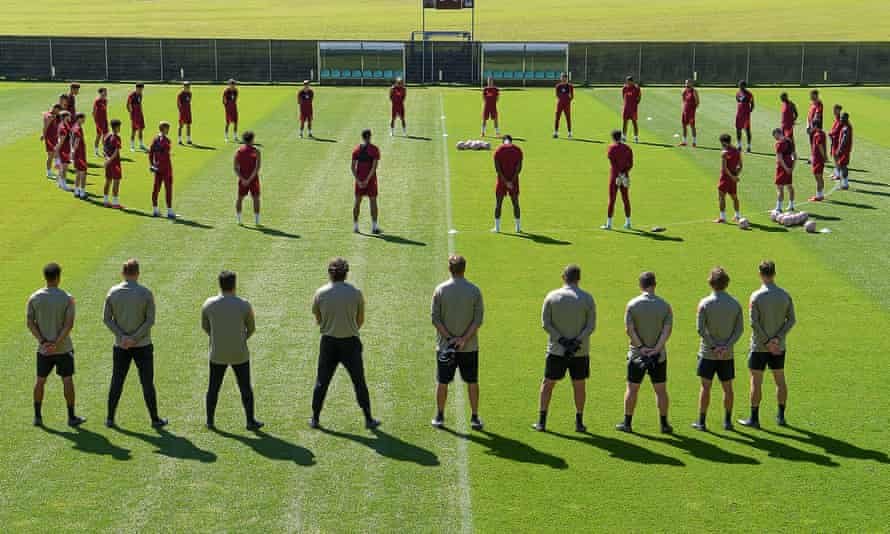 The Liverpool team and backroom staff observing a 97-second silence for Andrew Devine.