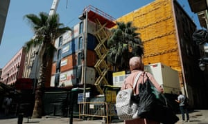 People walk by the construction site of the first building built with shipping containers in Barcelona.