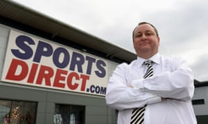 Mike Ashley stands cross-armed next to a Sports Direct sign