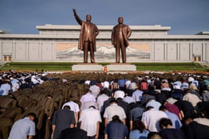 People bow before statues of the late North Korean leaders Kim Il-sung (left) and Kim Jong-il in Pyongyang, North Korea