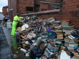 Flood-damaged books are left piled outside a Carlisle home on 11 December