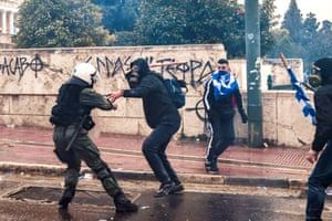 A riot police officer backs away from a protester about to strike with a long staff in Athens