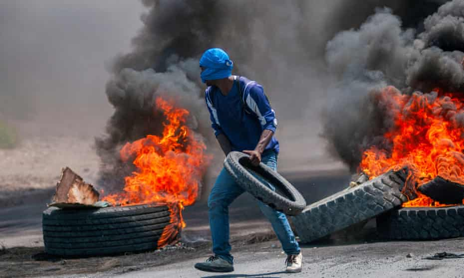 A demonstrator builds a barricade of flaming tyres during protests in Port-au-Prince on 17 September.