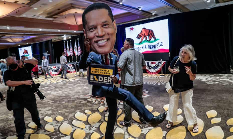 A supporter parades a cutout picture of Larry Elder at the candidate's California recall election party at the Orange County Hilton.