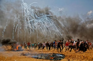 Teargas canisters fired by Israeli security forces explode above Palestinian demonstrators as they run for cover