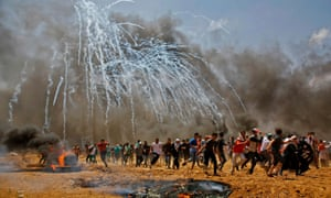 Palestinians run for cover from tear gas during clashes with Israeli security forces.