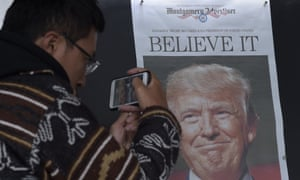 Zheng Gao, from Shanghai, China, takes a picture of the front page of a newspaper featuring Donald Trump.