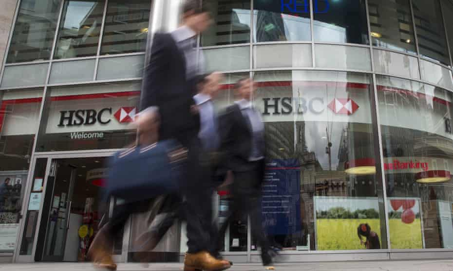 People walk past a branch of HSBC bank in central London