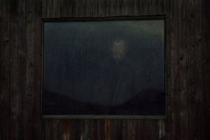 Slava stands at the window of his house during the rain