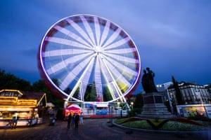 An illuminated ferris wheel at a summer carnival held on the bank of Lake Leman, Geneva