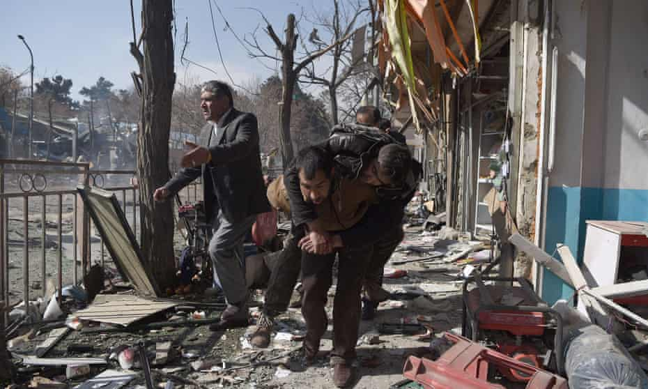 Volunteer rescue workers carry a man away from the scene of a bombing in Kabul, Afghanistan