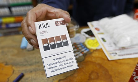 A cashier displays a packet of tobacco-flavored Juul pods at a store in San Francisco.