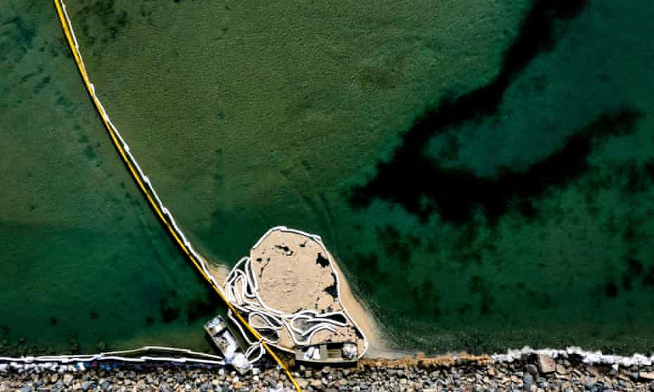 An aerial view of oil booms holding back contaminated water at the Talbert marsh in Huntington Beach, California, on Sunday.