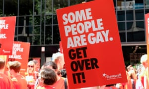 People marching in the sun with the poster 'Some people are gay. Get over it!' on a stick