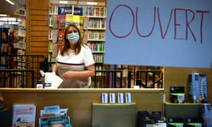 "A bookseller wearing a face mask stands next to an ""Open"" sign at a bookstore in Neuilly-sur-Seine in France."