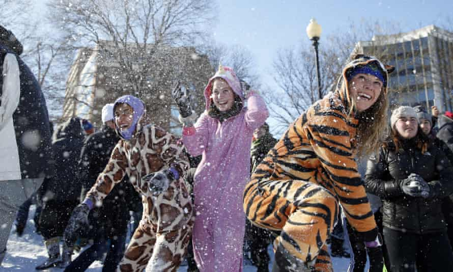 Young ladies wear animal onesie pyjamas during an snowball fight