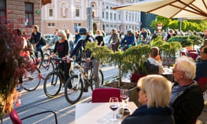 People having drinks on terraces look at Slovenian citizens, some wearing protective masks, riding their bikes as they block the centre of capital Ljubljana in protest, May 8, 2020.