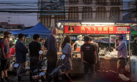 Nightime shot of customers lining up next to the Cowgirl's street food cart in Chiang Mai, Thailand.