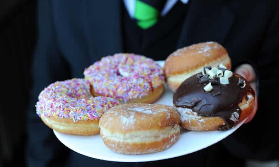 School boy holidng a plate of five glazed doughnuts