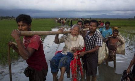 Rohingya refugees carry an elderly man as they cross the border into Bangladesh.