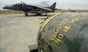 A British Royal Air Force Harrier GR7 taxis past a bomb-trolley of cluster bombs prior to them being loaded at its base in Kuwait in 2003.
