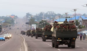 Military trucks carrying Congolese troops drive through a main street after violence in Kinshasa