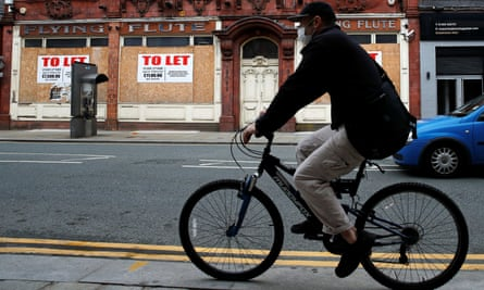 A man rides a bike past a boarded-up shop in Bolton