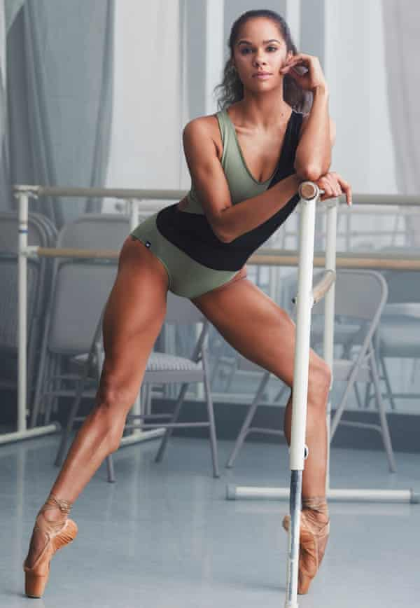 Misty Copeland, in a green and black leotard, leaning against a bar in a studio, her muscular legs evident as she stands on pointe