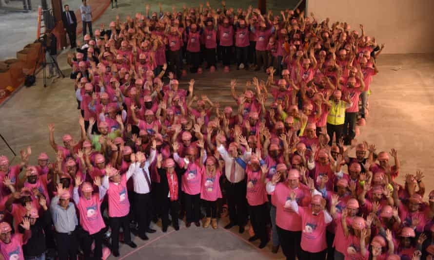 workers create massive pink ribbon