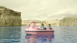 Two men on a swan boat on a lake