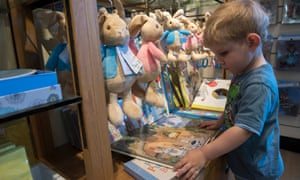 Young boy looks at Peter Rabbit books for sale in the Hill Top gift shop, in the Lake District.