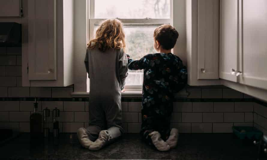 Two children looking out the window at the rain (posed by models)
