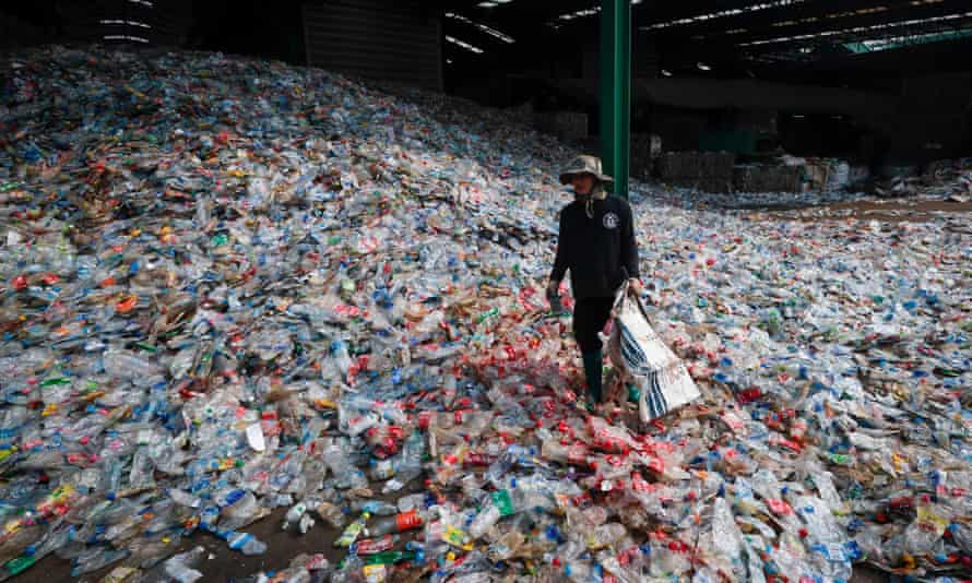A worker sorts through plastic bottles at the recycling plant near Bangkok in Thailand.
