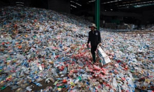 A migrant worker sorts through plastic bottles at a plant in Samut Sakhon, Thailand