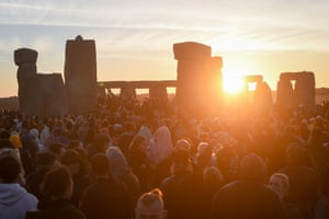 The sun breaks the horizon and shines through the stones at Stonehenge onto crowds of people