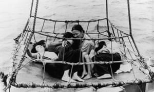 Vietnamese 'boat people' refugees huddle together on a tarp as they are airlifted out of the sea during the Vietnam War, 1960s. (Photo by Express Newspapers/Getty Images)