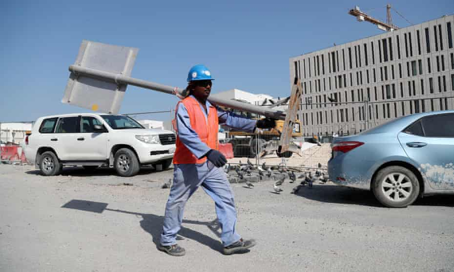 A migrant worker carries a pole at a World Cup construction site in the Qatari capital Doha.