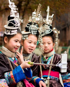 Douzhai, China. A group of young girls take a photo in their traditional costumes during a spring celebration in southwest Guizhou province