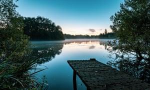 Chorlton water park with lake and jetty at sunrise.