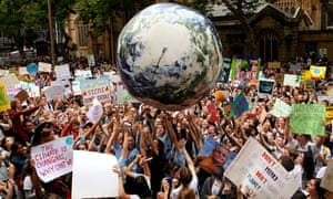 An inflatable planet Earth is bounced around the crowd during a student climate change strike in Sydney on Friday.