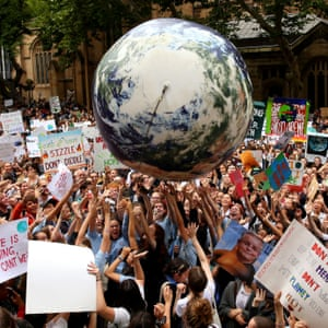 An inflatable planet earth is bounced around the crowd during a Climate Change Awareness rally at Sydney Town Hall.