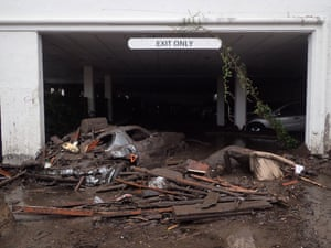 Damaged vehicles carried by mudflow and debris at the exit of the parking garage of the Montecito Inn