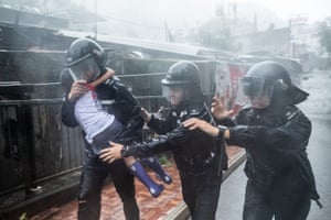 Police officers carry a girl out of a collapsed school in Hong Kong