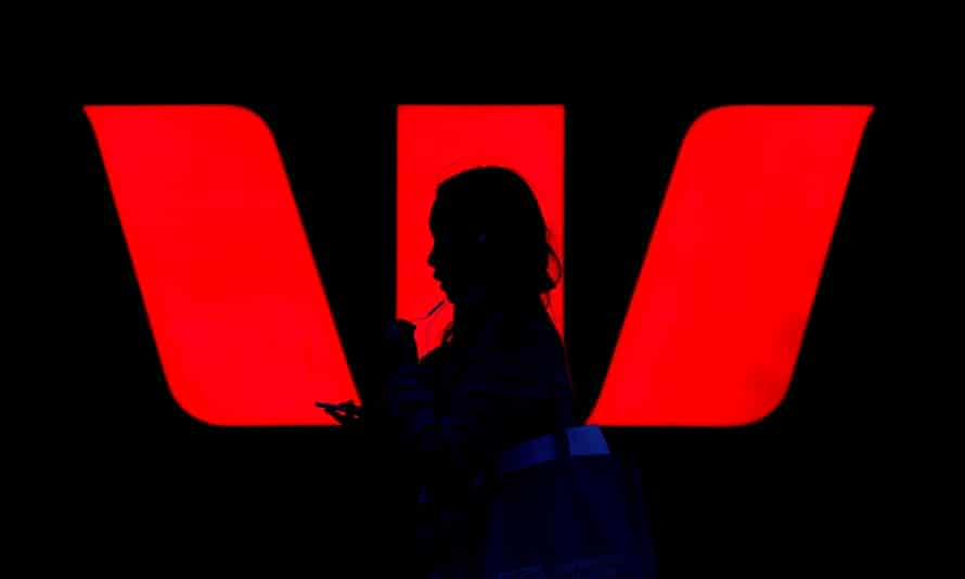 A woman walks past an illuminated logo for Westpac
