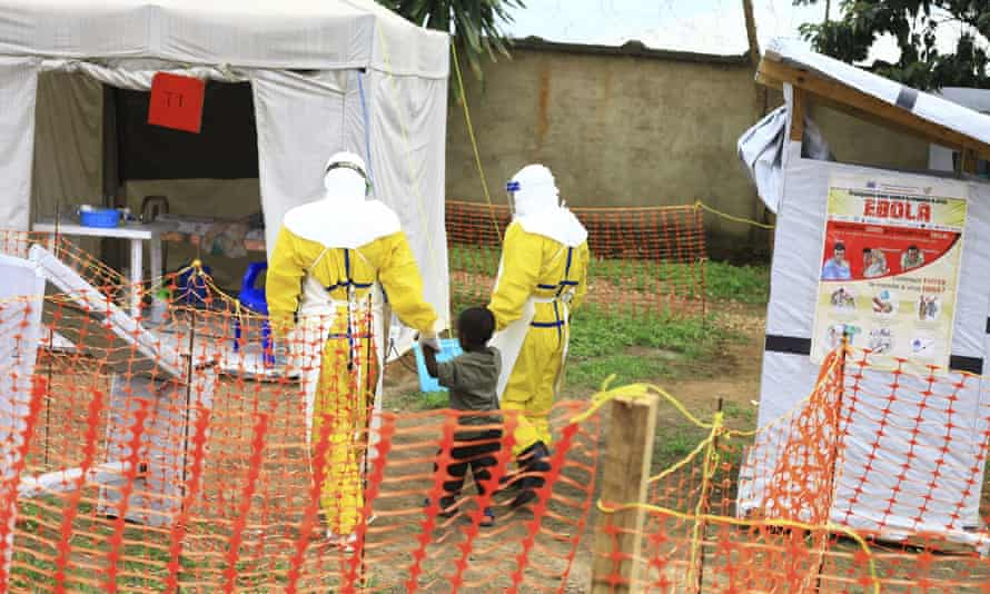 Health workers escort a young boy suspected of having the Ebola virus to a treatment centre in Beni, in eastern DRC